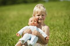 Stock Photo of Germany, Bavaria, Girl with baby doll in grass, smiling, portrait