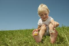 Germany,  Bavaria, Girl playing with flowers between toes on grass, smiling - stock photo