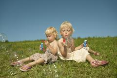 Germany, Bavaria, Girls sitting in grass and blowing bubbles Stock Photos