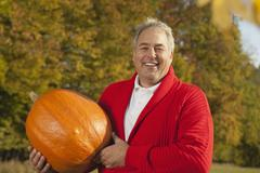 Stock Photo of Germany, Bavaria, Mature man holding pumpkin, smiling, portrait