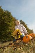 Stock Photo of Germany, Bavaria, Girl sitting on pumpkin with leaves, smiling, portrait