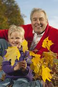 Germany, Bavaria, Grandfather and granddaughter in autumn, portrait , smiling - stock photo