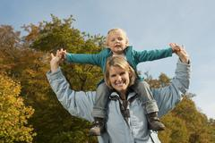 Stock Photo of Germany, Bavaria, Mother carrying daughter on shoulder, smiling