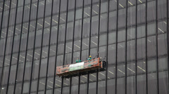 Workers clean and seal glass windows of highrise building Stock Footage