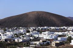 Spain, Canary Islands, Lanzarote, Uga, View of town and mountain in background Stock Photos