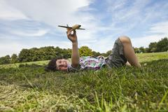 Germany, Bavaria, Boy playing with model airplane in park, smiling, portrait Stock Photos