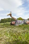 Germany, Bavaria, Boy playing with model airplane in park - stock photo