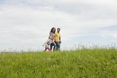 Germany, Bavaria, Family walking in grass at park Stock Photos