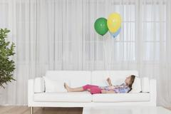Germany, Munich, Girl lying on couch with balloon - stock photo