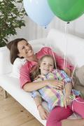 Stock Photo of Germany, Munich, Mother and daughter with balloon on couch, smiling