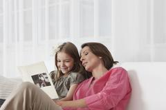 Germany, Munich, Mother and daughter reading book, smiling Stock Photos