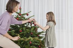 Germany, Munich, Mother and daughter decorating christmas tree Stock Photos
