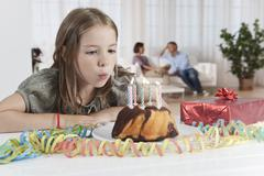 Germany, Munich, Girl blowing candles of birthday cake, parents in background - stock photo