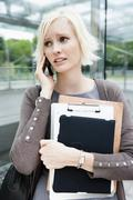 Germany, Bavaria, Munich, Young woman on phone waiting at metro station - stock photo