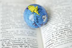 Germany, Close up of earth globe on open dictionary - stock photo