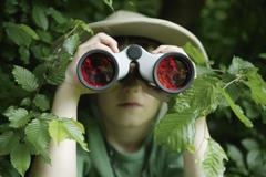 Germany, Bavaria, Close up of boy looking through binocular in forest - stock photo