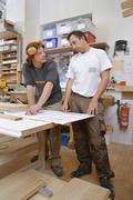 Germany, Upper Bavaria, Schaeftlarn, Carpenters preparing blue print Stock Photos
