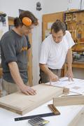 Germany, Upper Bavaria, Schaeftlarn, Carpenters preparing blue print - stock photo