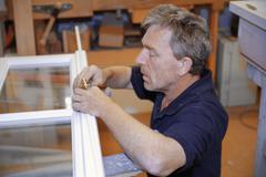 Stock Photo of Germany, Upper Bavaria, Schaeftlarn, Carpenter fixing window door handle