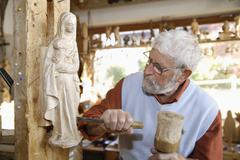 Germany, Upper Bavaria, Craftsperson carving statue - stock photo