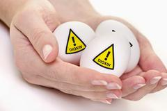 Stock Photo of Human hand holding eggs with warn sign of dioxin
