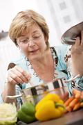 Close up of mature woman cooking fresh vegetables in pot Stock Photos