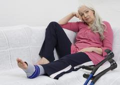 Germany, Duesseldorf, Woman with bandage sitting on sofa besides crutches - stock photo