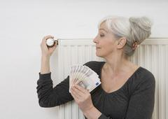 Germany, Duesseldorf, Woman holding banknotes and adjusting heater at home - stock photo