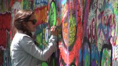 Female drawing a heart on the John Lennon Wall - Prague, Czech Republic Stock Footage