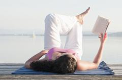 Stock Photo of Mid adult woman lying on jetty and reading book
