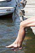 Stock Photo of Spain, Balears, Menorca, Woman sitting on jetty