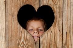 Austria, Salzburger Land, Alpine Pasture, Boy peeking from wooden door - stock photo