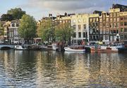 Stock Photo of Netherlands, Amsterdam, View of houses and boat with amstel canal