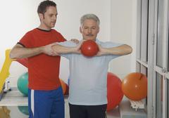 Germany, Nuremberg, Physical trainer giving training to senior man Stock Photos