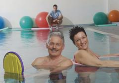 Stock Photo of Germany, Nuremberg, Couple in pool with man in background