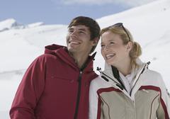 Austria, Tirol, Young couple looking away, smiling Stock Photos
