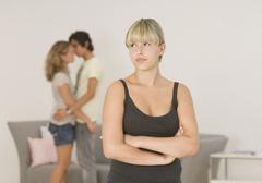 Young woman looking away with couple in background Stock Photos