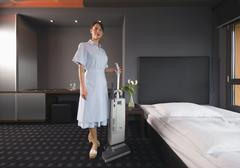 Germany, Maid with vacuum cleaner in a hotel room Stock Photos