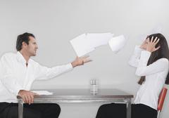 Business man throwing papers with woman head in hand Stock Photos