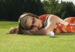 Saksa, nuori nainen lepää golfkenttä Kuvituskuvat