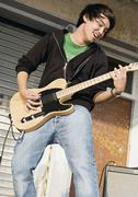 Germany, Augsburg, Young man playing an electric guitar - stock photo
