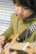 Germany, Augsburg, Young man playing an electric guitar Stock Photos