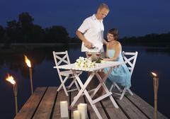 Germany, Augsburg, Couple enjoying wine on dock at dusk Stock Photos