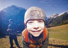 Austria, Boy smiling with mid adult man in background Stock Photos