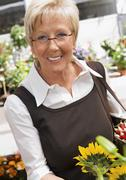 Germany, Augsburg, Mature woman doing shopping of flowers - stock photo