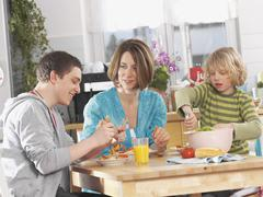 Germany, Augsburg, Mother and children eating pasta - stock photo
