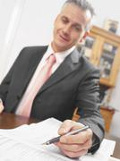 Stock Photo of Business man offering pen to sign contract