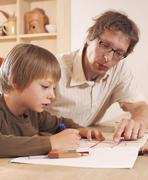 Stock Photo of Father and son doing homework