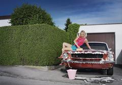Germany, Augsburg, Young woman washing her vintage car Stock Photos