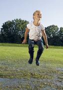 Girl jumping in puddle - stock photo